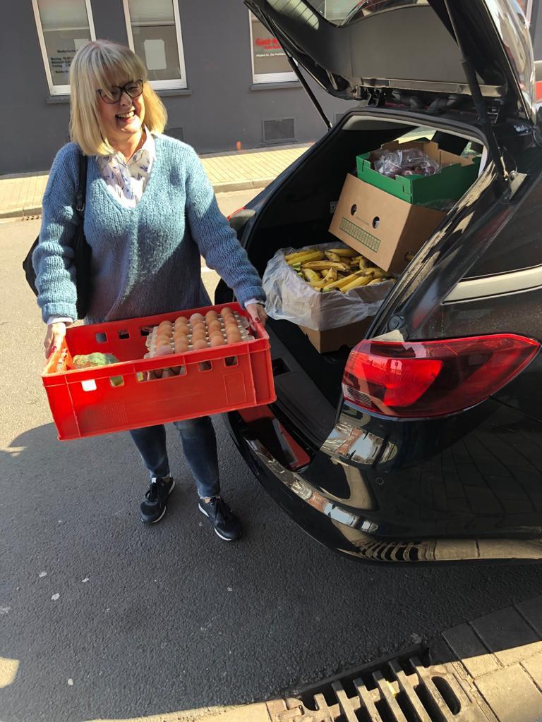 Unsere 1. Vorsitzende trägt eine Kiste mit frischen Eiern und grünem Gemüse