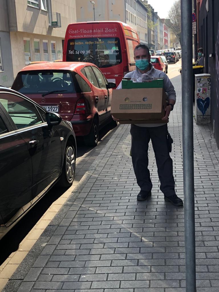 Ein Mitarbeiter trägt einen Karton voller Lebensmittel.