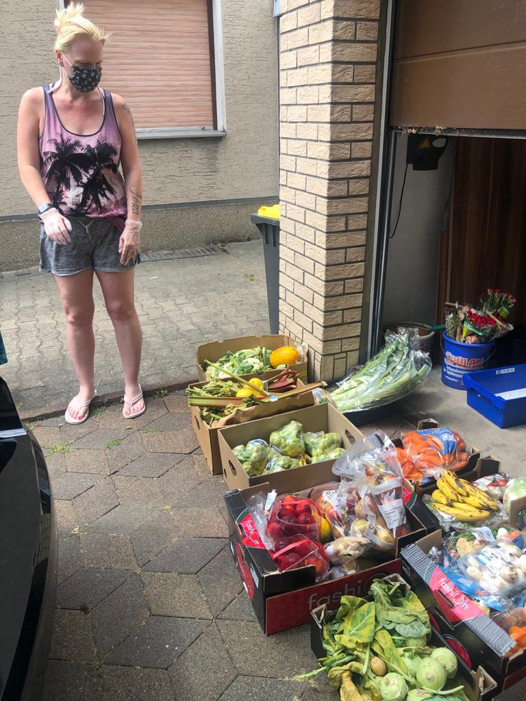 Eine Mitarbeiterin hat die gelieferten Lebensmittel ausgeladen und vor dem Garagentor aufgestellt.
